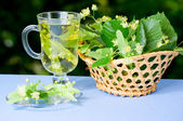 Taza de té de tilo y canasta con flores — Foto de Stock
