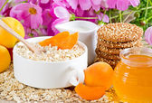 Oatmeal with apricot, milk jug, cookies, honey and flowers — Stock Photo