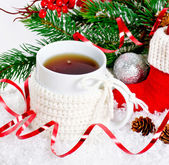 Cup of tea wearing a knitted sweater standing on snow — Stock Photo