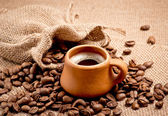 Coffee beans and clay cup — Stockfoto