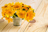 Yellow flowers in a pail on the wooden table — Stock Photo