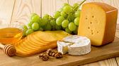 Натюрморт сыр, мед, грецкие орехи и виноград — Стоковое фото