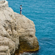 Stock Photo: Boy fishing on rock at Sea