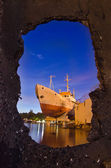 Ship on shore in night harbor - stone frame — Stock Photo