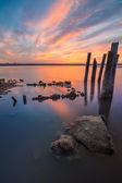 Unusual pillars in the water on the background of colorful sky — Stock Photo
