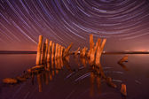 Pillars in the water at night on a background star trails — Stock Photo