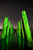 Unusual poles in the water at night on a background stars — Stock Photo