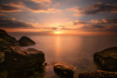Beautiful ocean sunrise - calm sea and boulders stone coastline  — Stock Photo