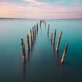Poles in the water -  on sunset clouds and ocean — Stock Photo