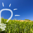 Ecological renewable idea of a light-bulb on a greenfield and blue sky — Stock Photo