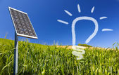 Ecological renewable solarpanel over greenfield and blue sky — Stock Photo