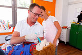 Doctor Dentist explains a teenage girl how she can clean the toy — Foto de Stock