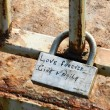 "A padlock with caption ""Love forever Gina+Naila"" attached to the — Stock Photo"