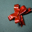 Royalty-Free Stock Photo: Red bow on a green background