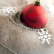 A red Christmas ball and snowflakes — Stock Photo