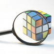 Loupe and cube rubik - Stock Photo