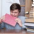 Crazy student gnaws red book — Stock Photo