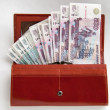 Orange leather wallet full of one hundred roubles - Stock Photo