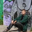 Man sitting  near a graffiti wall - Foto de Stock  