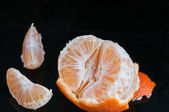 Half peeled tangerine with rind and two slices — Stock Photo