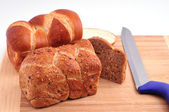 Two loaves of bread and a knife on a board — Stock Photo