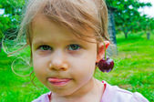 Girl with a sweet cherry on the ears — Stock Photo