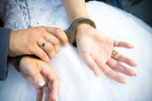Wedding rings with the couple — Stock Photo