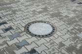 Sewer manhole in the pavement — Stock Photo