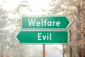 Signpost on two sides - Welfare or Evil — Stockfoto