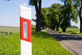 Road sign post on the road a distance — Stock Photo