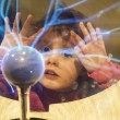 Girl looks into plasma ball - Stock Photo