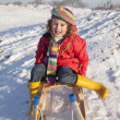 Laughing girl on a sledge — Stock Photo