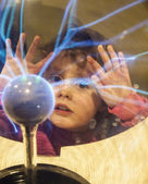 Girl looks into plasma ball — Stock Photo