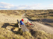 Small boy sitting next to bike in dunes — Stock Photo
