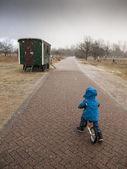 Menino em uma bicicleta em uma chuva de granizo — Foto Stock