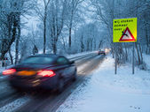 Car passes warning sign in a snow storm — Stock Photo