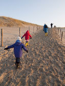 Young family leaving the beach — Foto Stock