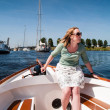 Woman at the tiller of a motor boat — Stock Photo