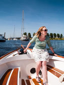 Woman at the tiller of a motor boat — Stockfoto
