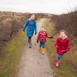 Woman and two small children walking along a path through dunes — Stock Photo #39312603