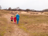 Woman and two small children walking in a dunes in winter — Stock Photo