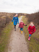Woman and two small children walking along a path through dunes — Stock Photo