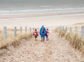 Woman and two small children walking down to the beach — Stock Photo