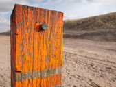 Beach post with sea level marker — Stock Photo