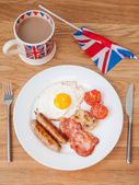 Full english breakfast with cup of tea and british flag — Stock Photo