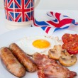 English breakfast with cup of tea and british flag behind — Stock Photo