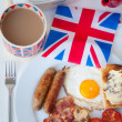 Full English breakfast with cup of tea, toast and british flag — Stockfoto