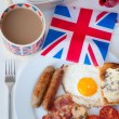 Full English breakfast with cup of tea, toast and british flag — Stok fotoğraf