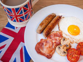 Close-up of Bacon and eggs with cup of tea and british flag — Stock Photo