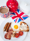Bacon, eggs and sausages with cup of tea, teapot, toast and bri — Stock Photo